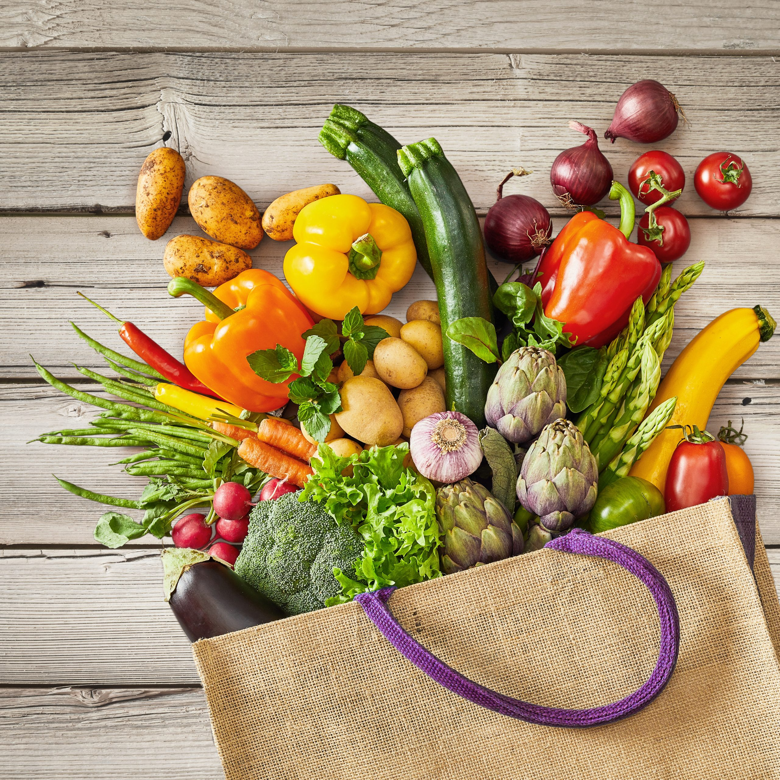 Grocery bag with purple handle that is spilling vegetables while on top of rustic wooden bench background