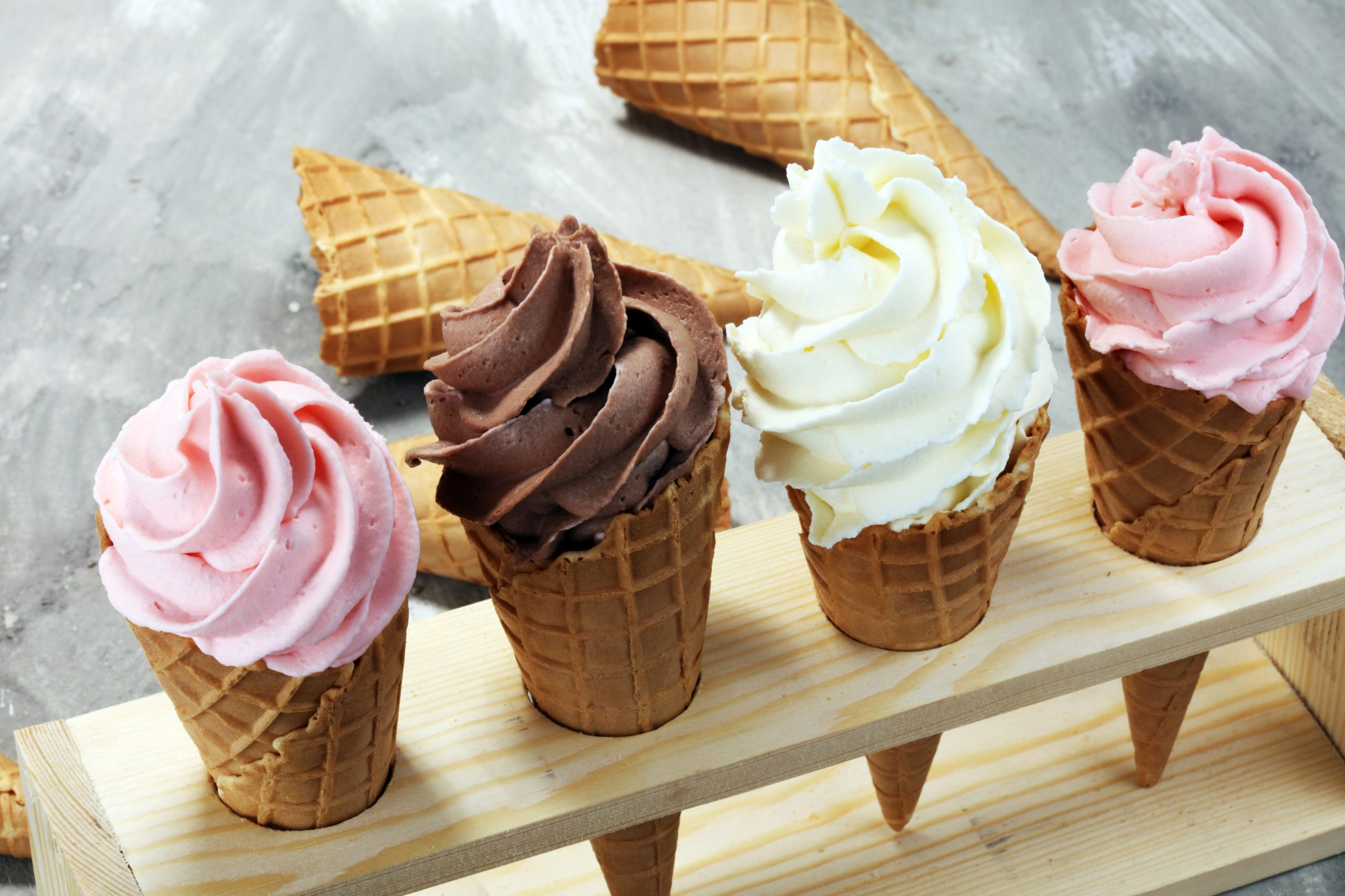 Vanilla frozen yogurt or soft ice cream in waffle cone and strawberry, raspberry and chocolate softice cream