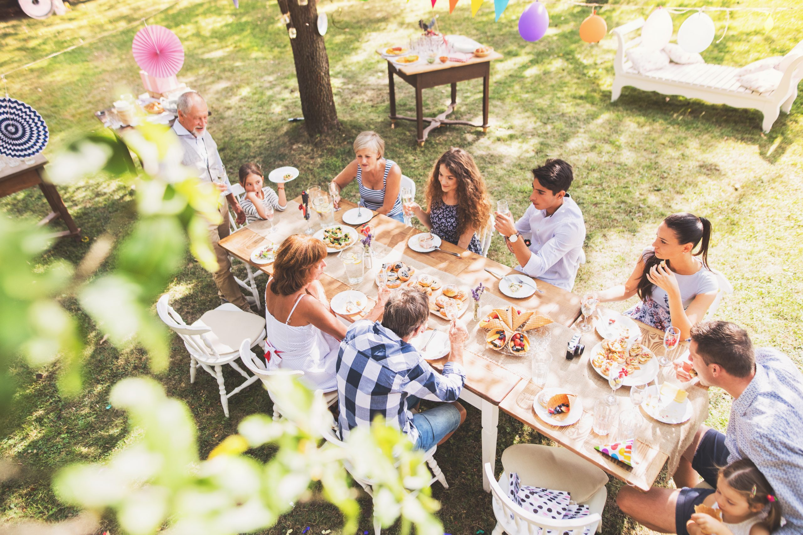 Family celebration outside in the backyard. Big garden party. High angle view.